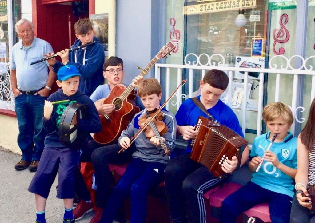 A groupf children playing traditional Irish musical instruments at a street session outside McNeela Instruments Pop-Up shop in Miltown Malbay