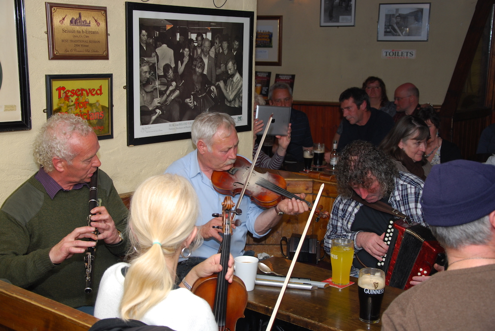A group of musicians, playing accordion, fiddle, flute playing in a pub session in Doolin County Clare