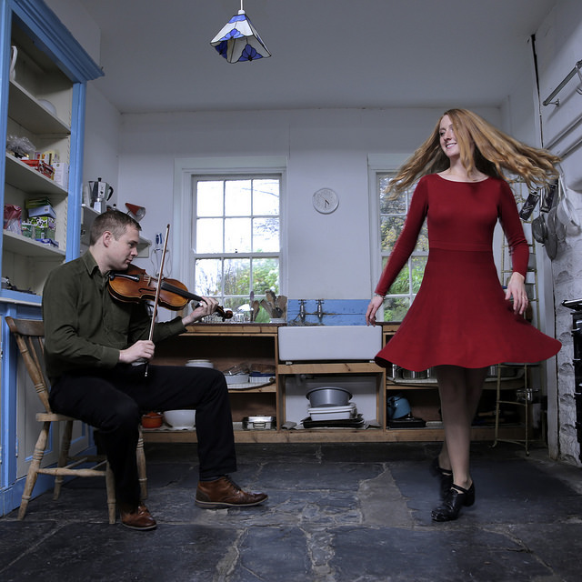 Ciaran playing fiddle and Caitlín Nic Gabhann dancing on flagstone kitchen