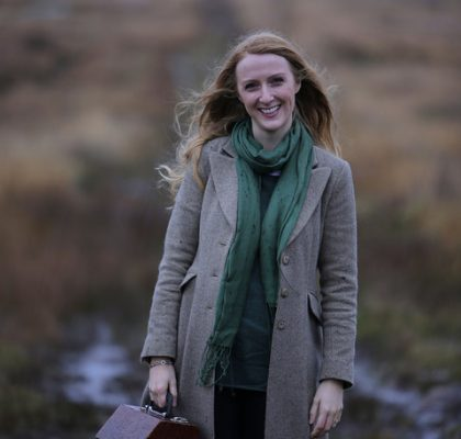 Caitlín standing in a Donegal Bog holding her wooden concertina case
