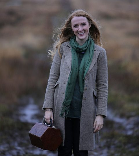 Traditional Irish Music - Caitlín Nic Gabhann standing in a Donegal Bog holding her wooden concertina case