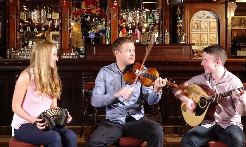 Caitlín Nic Gabhann (concertina and dance) and Ciarán Ó Maonaigh (fiddle) along with Cathal Ó Curráin (vocals, fiddle & bazouki) in a pub