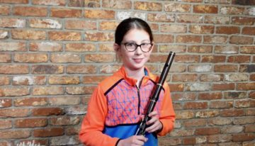 Young Irish Flute player, Lauren Carr, stands in front of brick wall of McNeela Instruments Studio