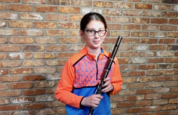 Young Irish Flute player, Lauren Carr, stands in front of brick wall of McNeela Instruments Studio with her Sam Murray flute