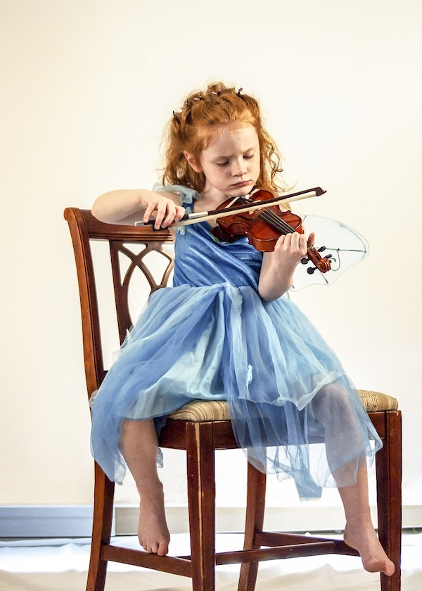 A young redheaded girl plays the fiddle seated on a chair