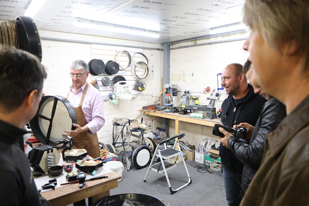 Paraic and the Band in the workshop, Paraic is taping a bodhrán
