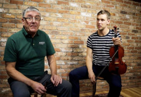 Paraic McNeela and Liam O'Connor sitting in the McNeela Instruments Studio with whistle and fiddle/violin