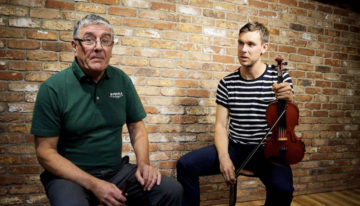 Paraic McNeela and Liam O'Connor sitting in the McNeela Instruments Studio with whistle and fiddle/violin ready to play the Kesh Jig