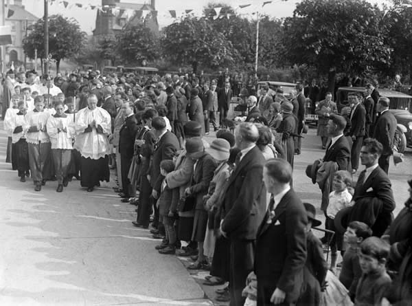 Procession of priests watched by onlookers in rural Ireland 1931