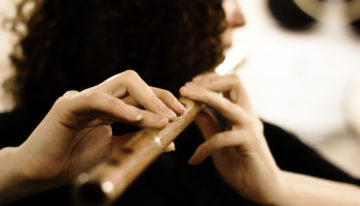 Woman playing Irish simple system wooden flute in rosewood