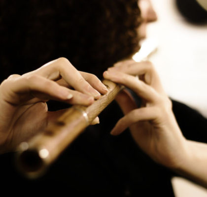 Irish musical instruments - Woman playing Irish simple system wooden flute in rosewood