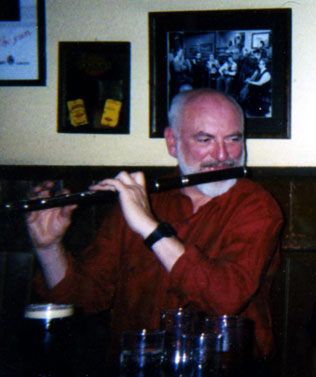 colour photo of man playing a large Pratten blackwood flute