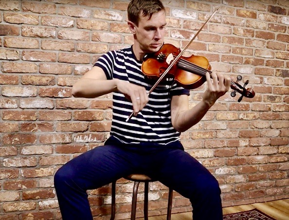 A young man sits on a stool and plays the Irish fiddle with a brick wall background taken at McNeela Music Ireland