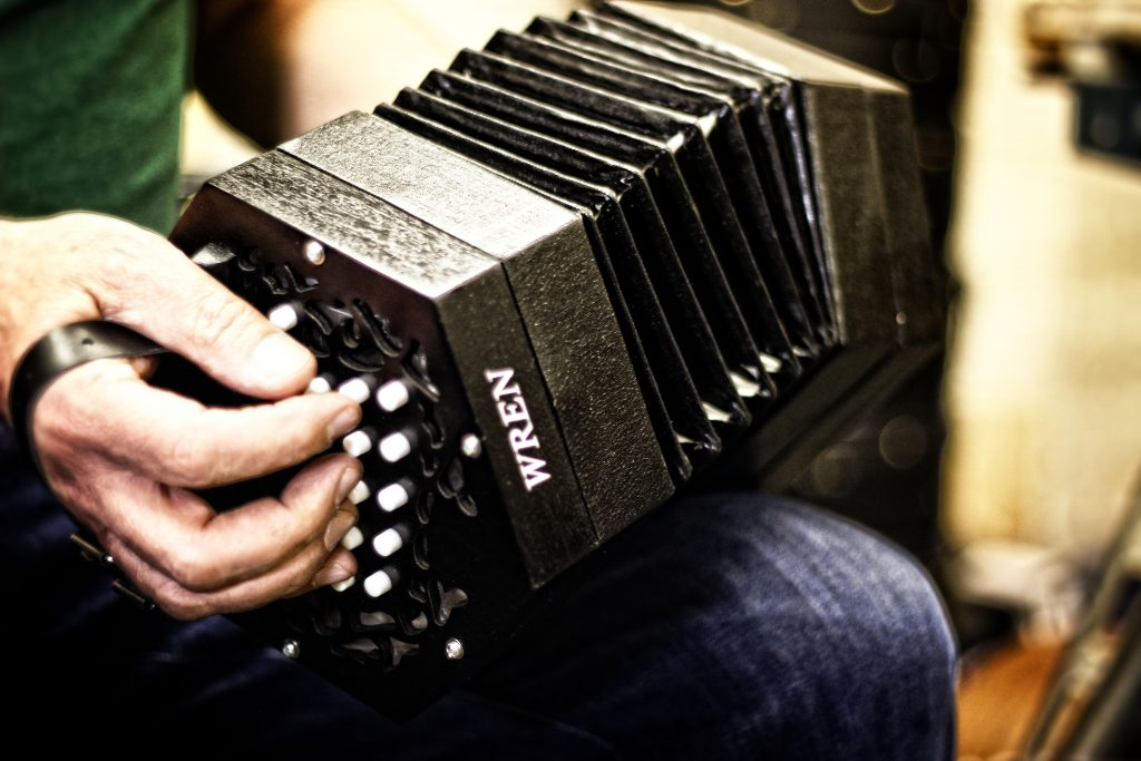The Anglo concertina is typically held by placing the hands through a leather strap, with the thumbs outside the strap and the palms resting on wooden bars. Most Asked Questions about Concertinas